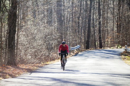 Cyclist riding bicycle on road in forest - CAVF39951