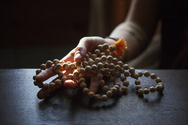 Cropped image of woman holding prayer beads in darkroom at home - CAVF39963