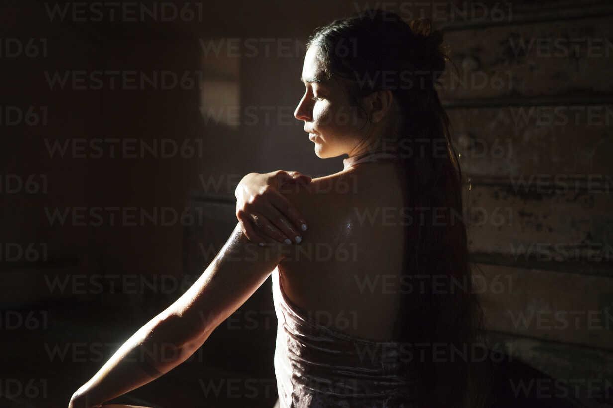 Rear view of woman applying oil to body in darkroom at home - CAVF39966 - Cavan Images/Westend61