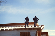 Low angle view of workers standing on roof beam against sky - CAVF39981