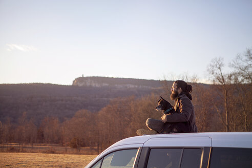 Side view of man sitting with dog on car roof against clear sky - CAVF39999