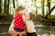 Brother kissing sister being carried by father at forest - CAVF40005