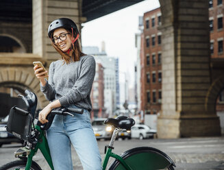 Happy woman using smart phone while standing by bicycle on street - CAVF40023