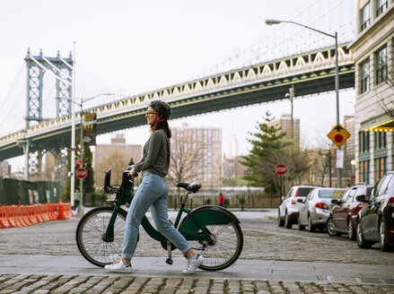 Side view of woman with bike share walking on street with Manhattan Bridge in background - CAVF40026