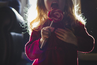 Midsection of girl eating lollipop at home - CAVF40056