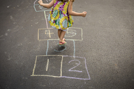 Low section of girl playing hopscotch on road - CAVF40068