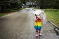 Girl carrying umbrella while standing on wet road - CAVF40071
