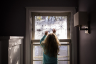 Rear view of girl drawing on condensed window at home - CAVF40080