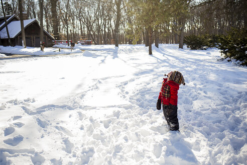 Side view of boy looking up while standing on snow covered field at yard - CAVF40083