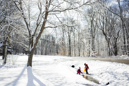 Siblings playing on snow covered field - CAVF40089