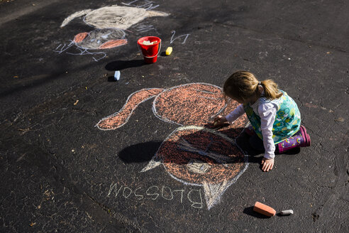 High angle view of girl drawing with chalk on asphalt - CAVF40101