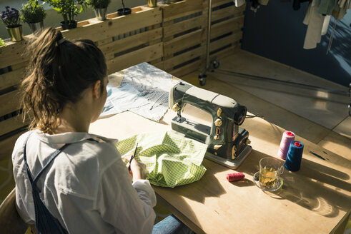 Back view of fashion designer at work in her studio - MOEF01010
