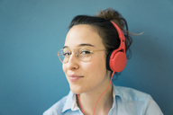Portrait of smirking woman listening music with headphones - MOEF01013