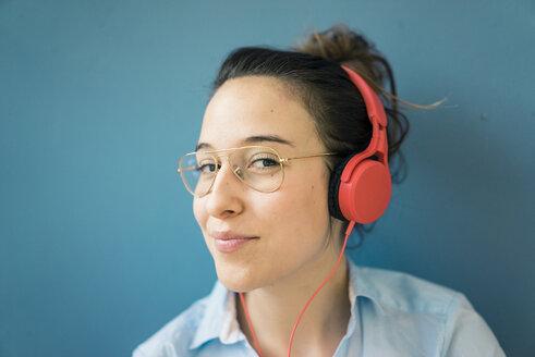 Portrait of smirking woman listening music with headphones - MOEF01013