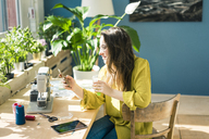 Fashion designer sitting at desk in her studio using smartphone - MOEF01028