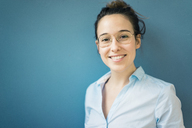 Portrait of smiling young woman wearing glasses in front of blue wall - MOEF01034