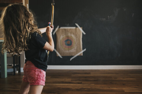 Side view of girl aiming arrow while standing at home - CAVF40122