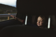 Cute boy with eyes closed enjoying road trip seen through vehicle seat - CAVF40161