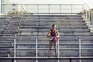 Thoughtful female athlete standing on bleachers - CAVF40209
