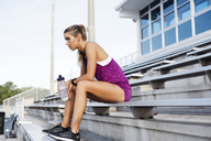 Side view of sporty woman sitting on bleachers at stadium - CAVF40212