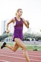Determined female athlete running on race track against sky - CAVF40218