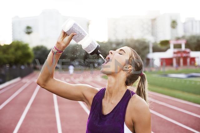 Female athlete drinking water on race tracks - CAVF40224 - Cavan Images/Westend61