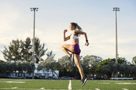 Side view of determined female athlete exercising on field - CAVF40227