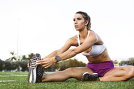 Confident female athlete touching toes while exercising on field - CAVF40230