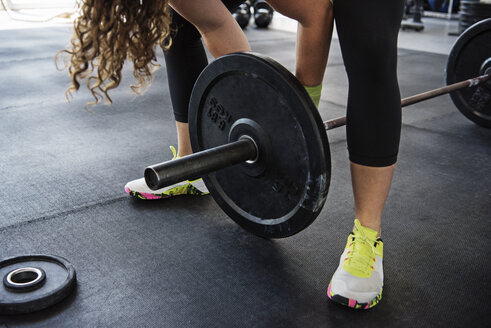 Midsection of woman exercising with barbell at crossfit gym - CAVF40233