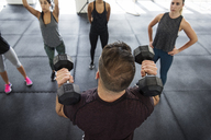 Instructor explaining athletes to lift dumbbells in crossfit gym - CAVF40239