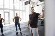 Instructor explaining female athletes in crossfit gym - CAVF40242