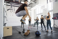 Instructor teaching athletes while dog lying in crossfit gym - CAVF40245