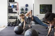 Determined athletes doing push-ups using dumbbells in crossfit gym - CAVF40254