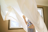 Playful girl playing with curtains at home - CAVF40302