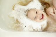 Overhead view of cheerful girl bathing in bathtub - CAVF40305