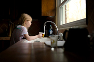 Girl filling cup with water in kitchen - CAVF40317