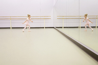 Girl practicing ballet in front of mirror at ballet studio - CAVF40323
