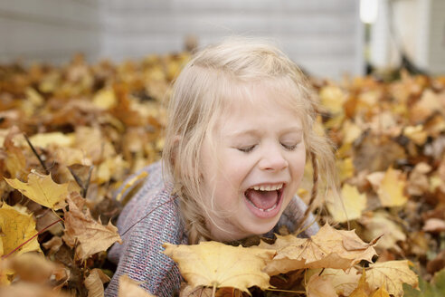 Cheerful girl playing with maple leaves during autumn - CAVF40335