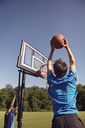 Boys playing basketball by trees against clear sky - CAVF40389