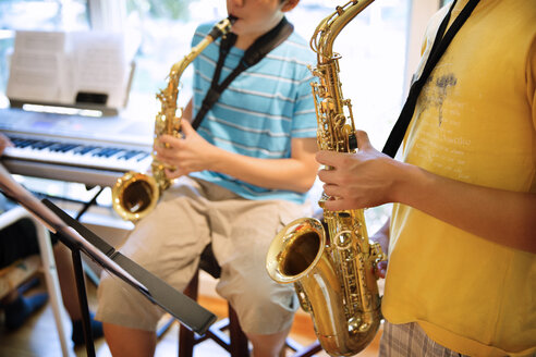 Boys practicing saxophones at home - CAVF40401