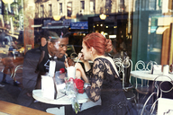 Happy couple enjoying drink in restaurant seen through glass - CAVF40437