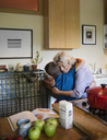 Happy woman embracing grandson while standing in kitchen at home - CAVF40467