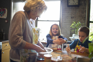 Happy children with grandmother mixing flour in kitchen - CAVF40470