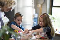 Children with grandmother preparing dough in kitchen - CAVF40473
