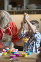 Boy with grandmother filling cupcake holders in kitchen - CAVF40491