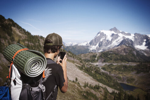 Hiker photographing mountains through smart phone against sky - CAVF40677