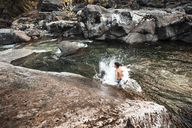 Hiker enjoying in river against rocks at forest - CAVF40686
