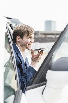 Smiling businessman using smartphone in car - UUF13414