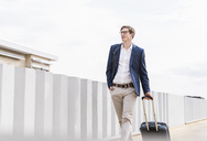 Confident businessman with rolling suitcase walking at parking garage - UUF13420