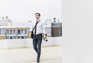 Businessman with takeaway coffee and skateboard walking at parking garage - UUF13429
